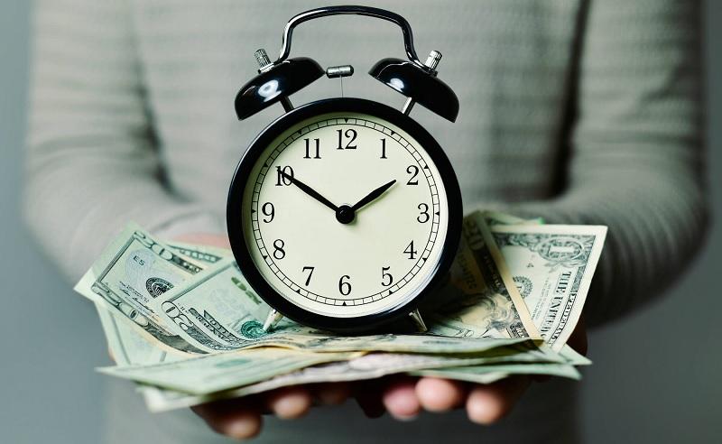 Держит деньги и часы в руках